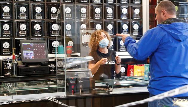 Una dependienta atiende a un cliente en un comercio de San Sebastián.