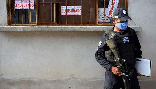 Un agente de la Policía estatal resguarda una tienda clausurada donde se vendía alcohol adulterado en el municipio de Jonacatepec, estado de Morelos (México).