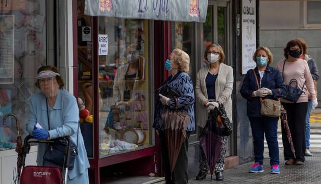 Varias mujeres con mascarilla hacían cola ayer, ante una mercería en el barrio de Triana de Sevilla.