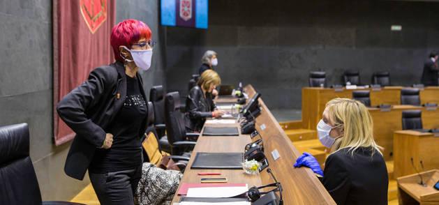 Foto de la consejera Santos Induráin (a la izquierda) habla con la portavoz socialista Patricia Fanlo antes del inicio de una sesión parlamentaria.