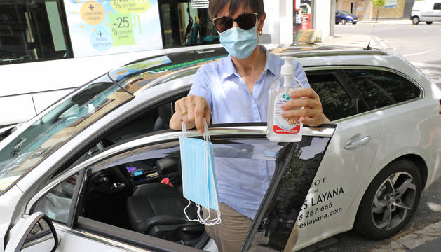 foto de Mari José Mendiburu, en su taxi, con las mascarillas que tiene para los pasajeros.