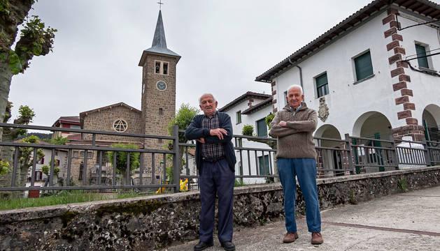Paulino y Rafael Larrea, hermanos de 90 y 83 años, junto a la escuela y la iglesia de Erro, frente a su casa.
