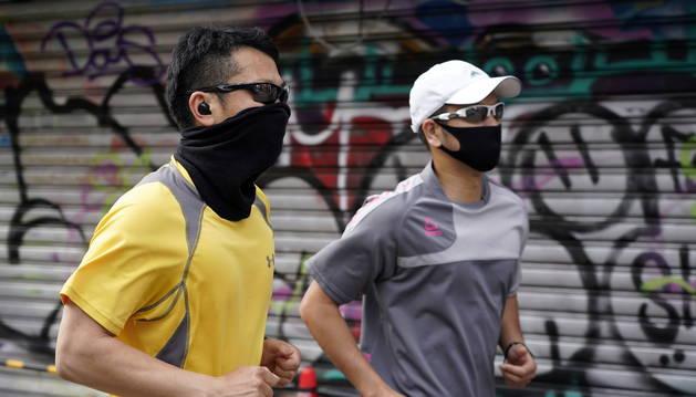 Foto de Dos hombres hacen ejercicio con mascarilla en Harajuku, Tokio.