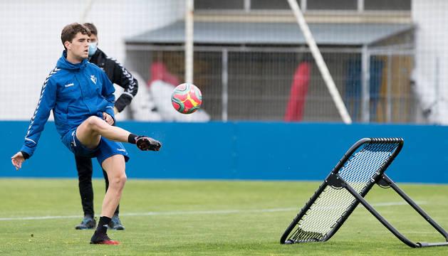Javi Martínez golpea el balón frente a una red reboteadora. Detrás, Bittor Alkiza.