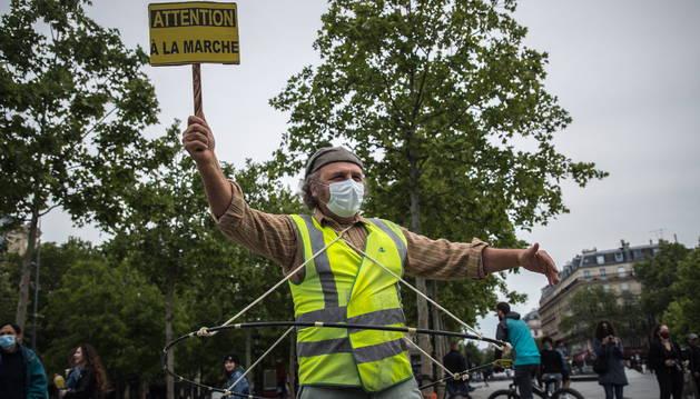 Foto de un hombre con un chaleco amarillo sostiene un cartel de protesta en París.