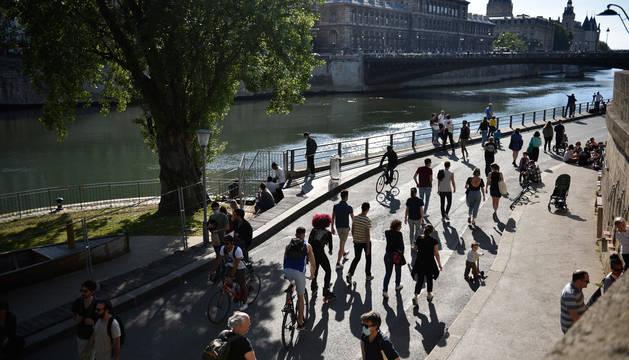 Personas pasean a orillas del Sena, en París.