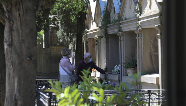 Foto de dos personas depositando flores en un panteón del cementerio.