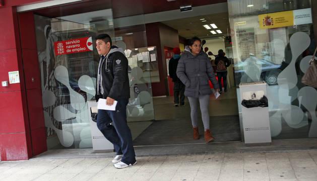 Un hombre y una mujer salen de una oficina de empleo.