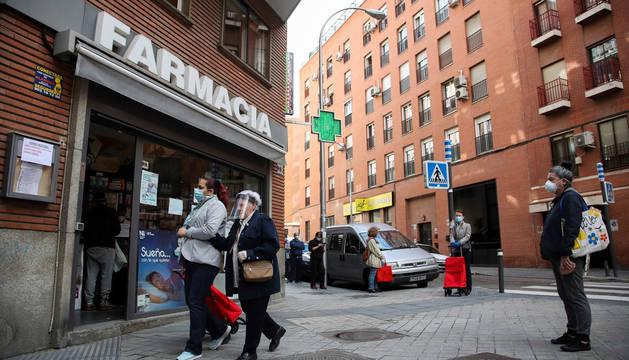 Fotos de varias personas con mascarillas haciendo turno para entrar en una farmacia en Madrid.