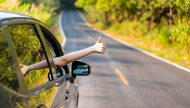 Una mujer hace una señal desde el interior de su coche
