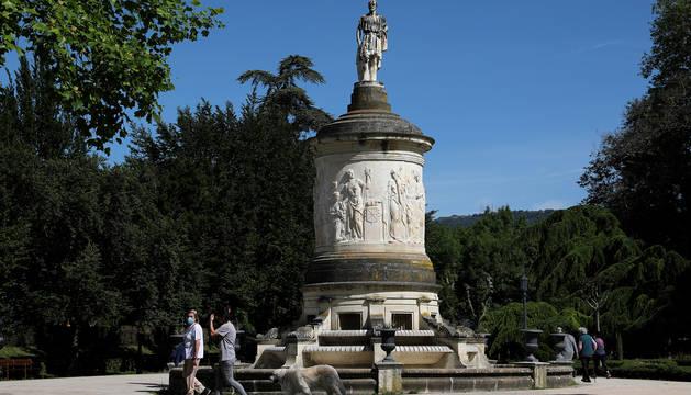 Dos mujeres pasean a un Golden Retriever frente al monumento a Gayarre en el parque de la Taconera de Pamplona