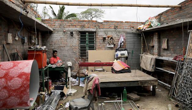 Una persona en el interior de su casa afectada por el paso del ciclón 'Amphan' en la localidad india de Bokkhali.