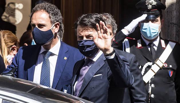El primer ministro italiano, Mateo Renzi, saluda protegido por una mascarilla antes de meterse en el coche oficial.