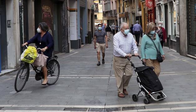 Varias personas cubiertas con mascarillas caminan por una calle del Casco Viejo de Pamplona.
