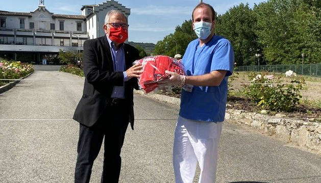 El presidente de Osasuna, Luis Sabalza, entregando las mascarillas.