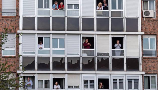 Personas asomadas a sus ventanas en un edificio de Estella.