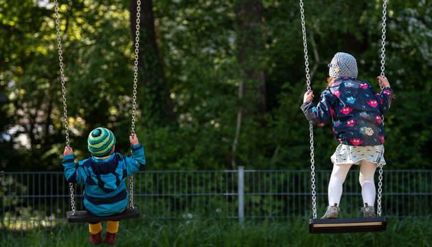 Dos menores se columpian en un parque de Munich, en Alemania, donde los parques ya han reabierto.