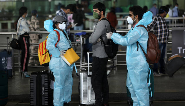 foto de Varios pasajeros vestidos con equipos de seguridad en un aeropuerto de India