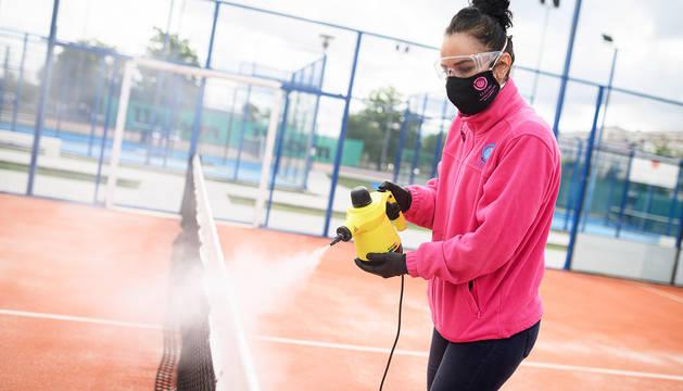 Una trabajadora de un club de pádel de Madrid desinfecta las instalaciones durante la pandemia.