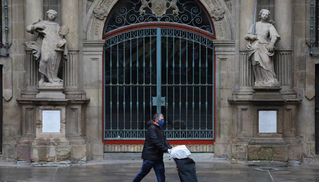 Un transeúnte pasa ante la fachada del Ayuntamiento de Pamplona el pasado mes de abril.