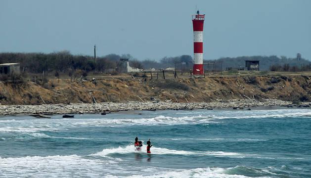 Tres jóvenes se bañan en una playa colombiana, destino turístico, vacía por la pandemia de coronavirus.