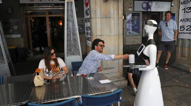 Foto del humanoide sirve una cerveza en la terraza del bar.