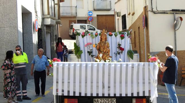 Foto de la Virgen de Gracia engalanada con flores y  sobre el camión de la brigada, en El Paredón