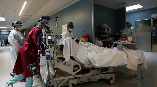 Sanitarios acompañan a un enfermo en la UCI del CHN.