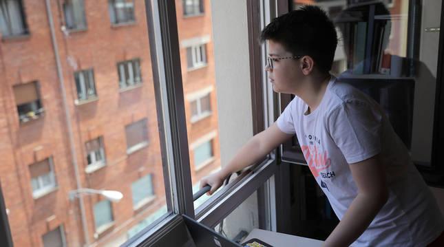 Un niño de 11 años mira a lo lejos por la ventana, después de consultar el ordenador.