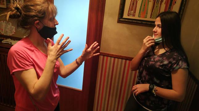 Pilar Rubio Benito, de 43 años y sorda, habla con su hija, Patricia Martínez (16), que se baja la mascarilla, en su casa de Peralta.