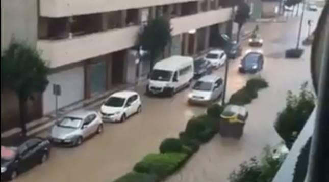 foto de Un contenedor es arrastrado por la fuerza del agua en una calle de Tudela inundada tras la tormenta