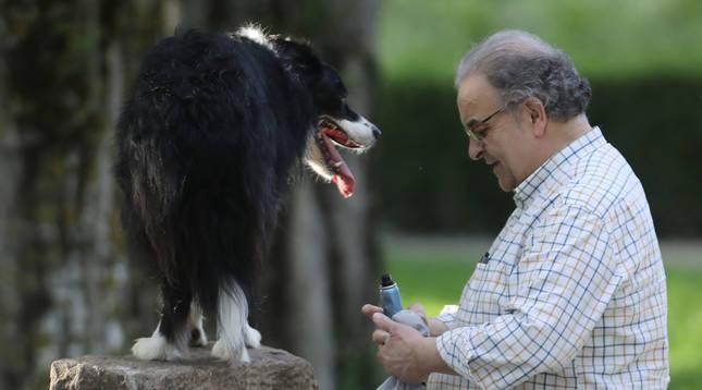 Un hombre con su perro subido a un monolito del paseo del Arga.