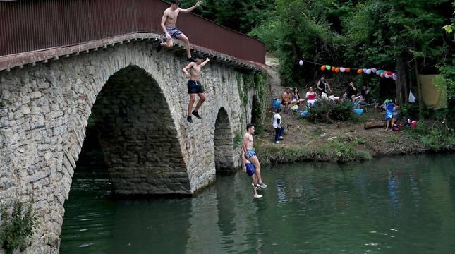 Varios jóvenes se lanzan al Arga desde el puente de Irotz, mientras otro grupo festeja en la orilla.
