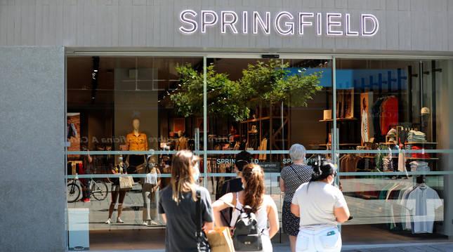 Un grupo de personas espera a la entrada de la tienda Springfield, en la avenida Carlos III.