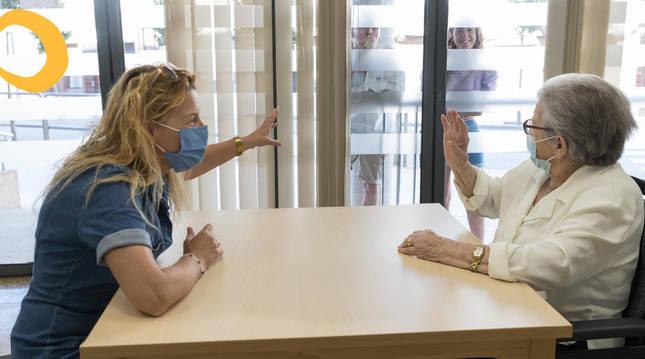 Ana Carmen Jaraba recibe la visita de su hija Lina y saluda a otros familiares a través del cristal.