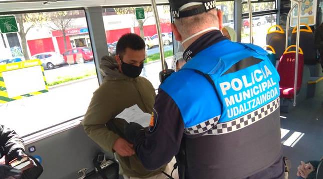 Foto de un agente de Policía Municipal realizando controles en un autobús urbano.