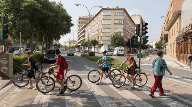 Cuatro jóvenes ciclistas cruzan un paso de peatones de la avda. Zaragoza que se hará mixto (peatón y bici).