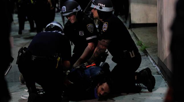 Tres agentes de la policía detienen a una persona durante los enfrentamientos en Nueva York.