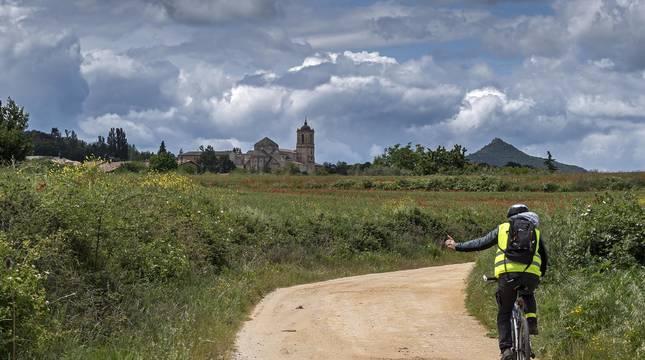 Un ciclista circula por una pista del entorno de Ayegui que lleva hasta el Monasterio de Irache, al fondo de la imagen.