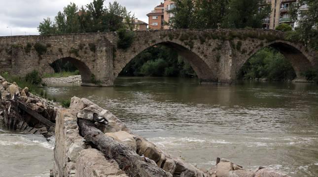 La presa de Santa Engracia con la escotadura central por donde se cuela el agua del río Arga desde hace más de dos años. Al fondo, el puente de Santa Engracia.