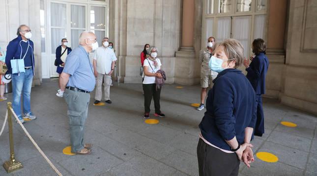 Varias personas cubiertas con mascarillas esperan respetando la distancia para visitar el Palacio Real en Madrid.