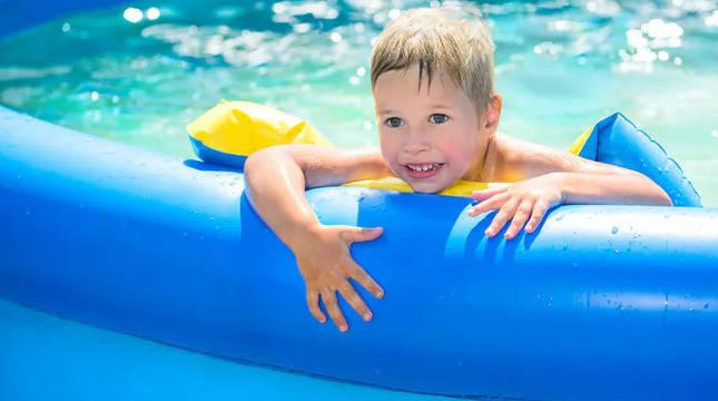 Un niño, en una piscina de plástico.
