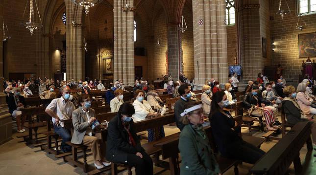 Los fieles que acudieron ayer a la catedral de Pamplona para celebrar el Corpus Christi, protegidos con mascarillas o pantallas.