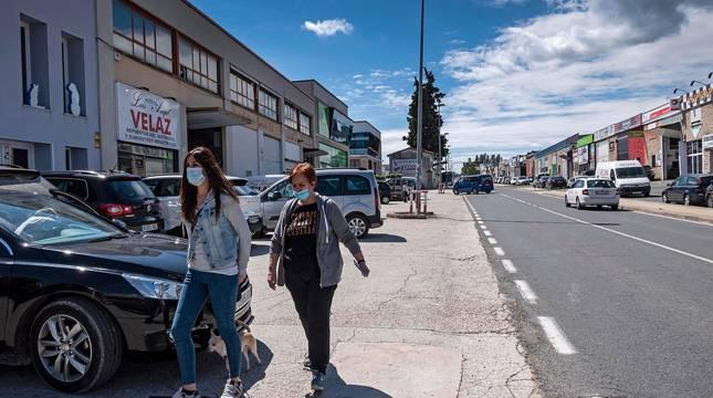 Dos personas caminan por el polígono de Merkatondoa de Estella con mascarilla.