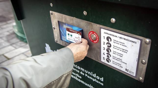 Una persona acerca su tarjeta a un contenedor en Azpilagaña.