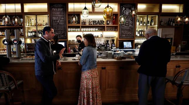 Varios clientes, en la barra de un bar de Pamplona este lunes.