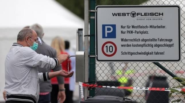 Una hombre se da gen hidroalcohólico antes de entrar a trabajar en Alemania.