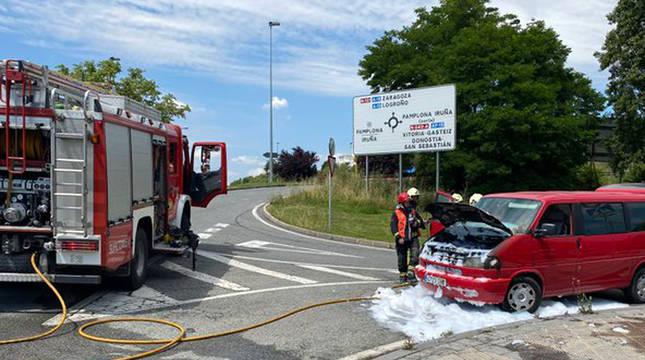 Los bomberos sofocan las llamas del coche.