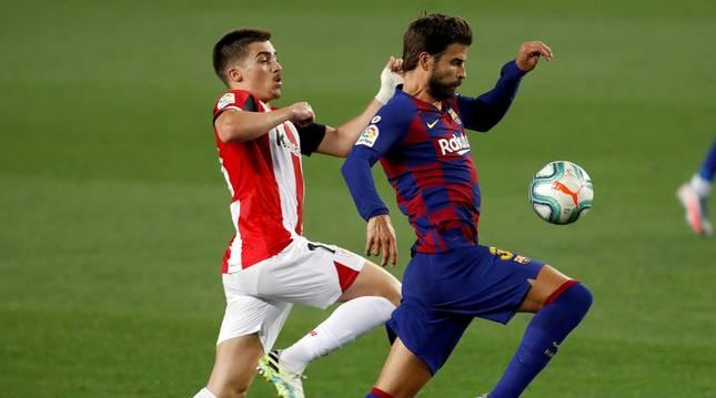El defensa del FC Barcelona, Gerard Piqué (d), disputa el balón ante el centrocampista del Athletic, Íñigo Córdoba