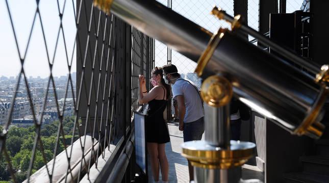 Foto de dos turistas observando París desde la Torre Eiffel, este jueves.